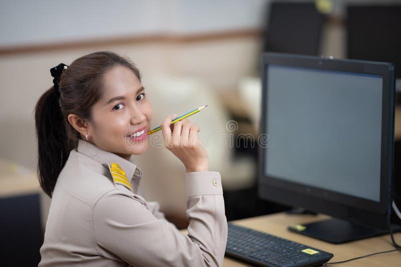 Ritratto dell'ufficiale tailandese di governo facendo uso del computer all'ufficio de immagini stock libere da diritti