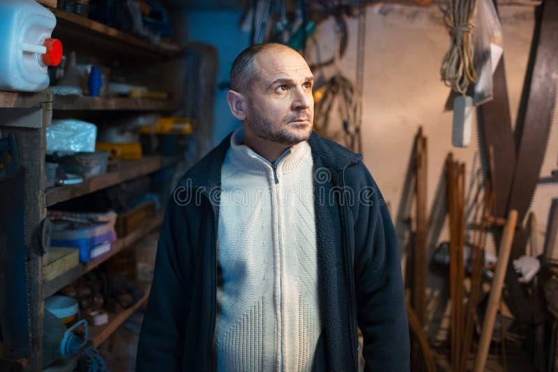 Ritratto dell'uomo adulto pensieroso nella sua stanza dell'officina immagini stock