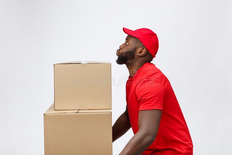 Ritratto dell'uomo afroamericano di consegna in camicia rossa lui scatole pesanti di sollevamento contro avere isolato sul fotografia stock libera da diritti