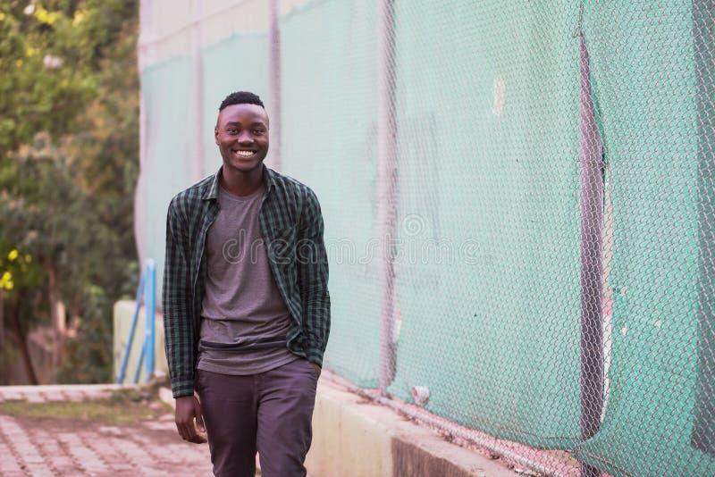 Ritratto dell'uomo afroamericano felice alla moda sugli abiti sportivi, camminata verde della camicia Modo di modello della via d fotografia stock libera da diritti