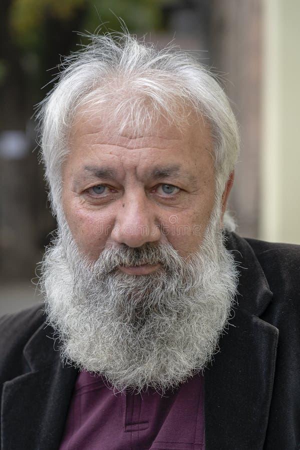 Ritratto dell'uomo anziano con una barba grigia in una chiesa ortodossa russa nel centro di Tbilisi, Georgia fotografia stock libera da diritti