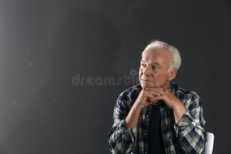 Ritratto dell'uomo anziano povero su fondo scuro fotografia stock libera da diritti