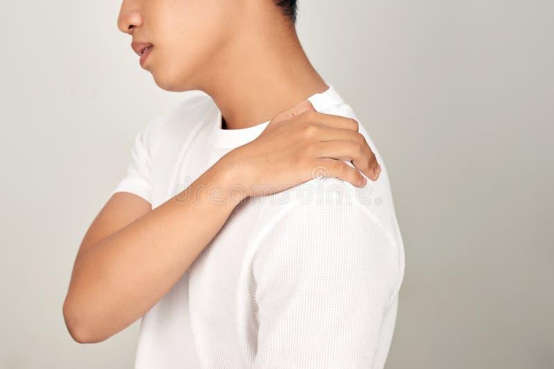 Ritratto dell'uomo asiatico bello con il fronte scomodo, soffrente dal dolore al collo Concetto di sanità e medico su bianco immagini stock
