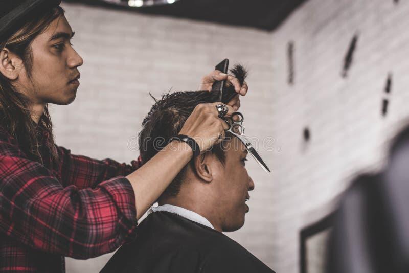 Ritratto dell'uomo asiatico con il lavoro marrone lungo dei capelli come barbiere con il costume immagine stock libera da diritti