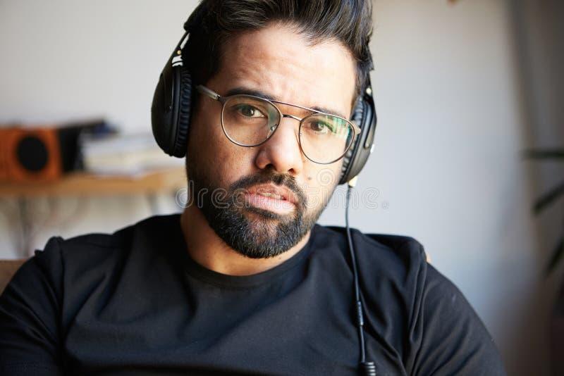 Ritratto dell'uomo barbuto bello in cuffie che ascolta la musica a casa Concetto di tempo di resto e di rilassamento vago fotografia stock
