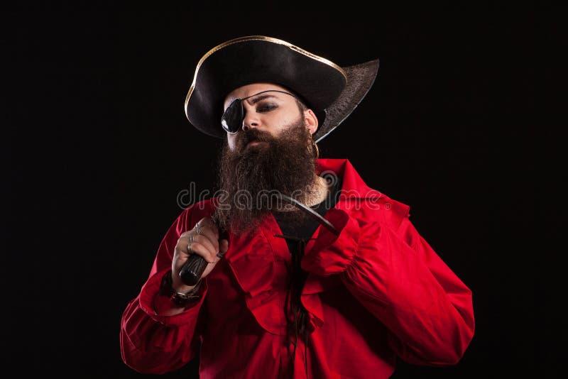 Ritratto dell'uomo barbuto bello in un costume del pirata che sembra serio nella macchina fotografica per Halloween fotografie stock