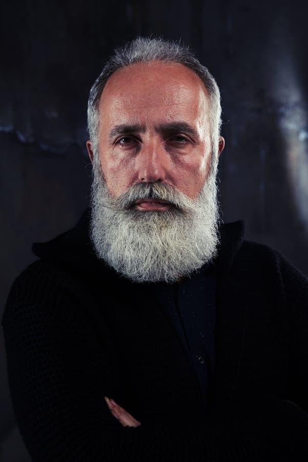 Ritratto dell'uomo barbuto maturo bello che esamina la macchina fotografica fotografie stock libere da diritti