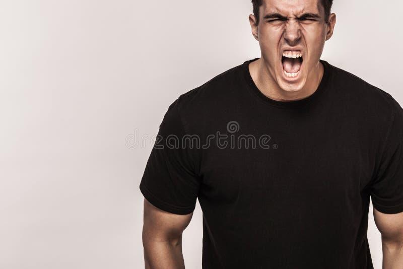 Ritratto dell'uomo bello alla moda in maglietta nera Fondo leggero con lo spazio della copia fotografia stock libera da diritti