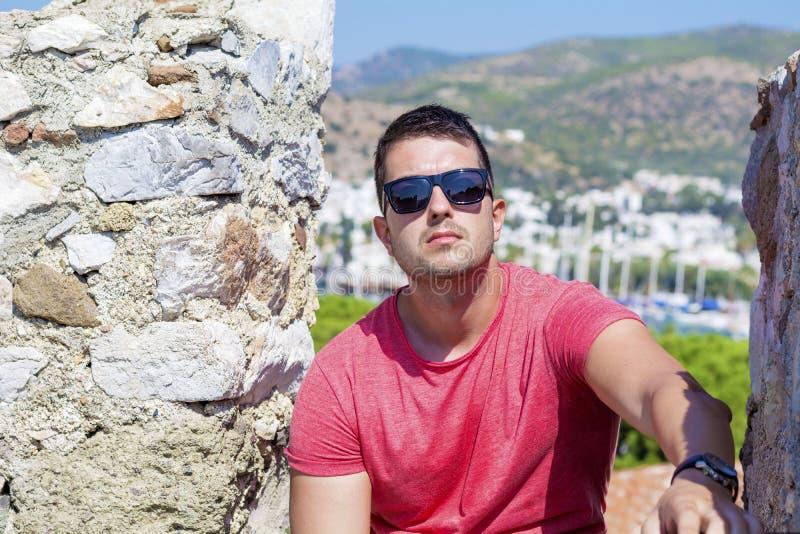 Ritratto dell'uomo bello con gli occhiali da sole neri su un fondo della località di soggiorno del mare fotografia stock libera da diritti