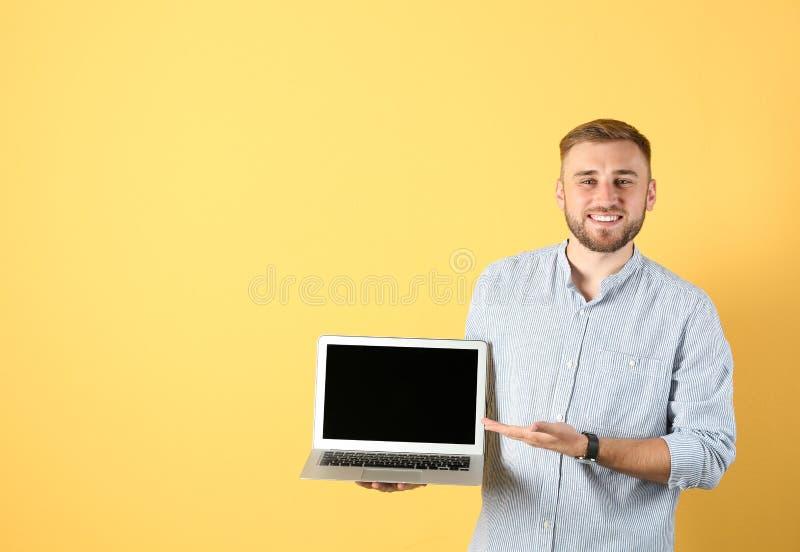Ritratto dell'uomo bello con il computer portatile immagini stock