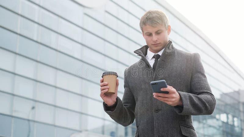 Ritratto dell'uomo bello di affari facendo uso dello smartphone e del bere immagine stock libera da diritti