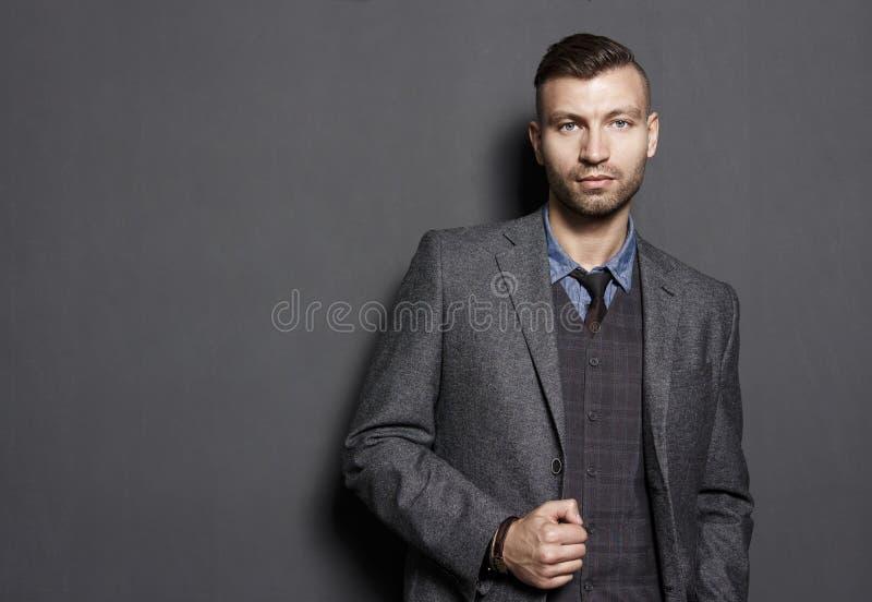 Ritratto dell'uomo bello sicuro alla moda in vestito sul fondo grigio della parete Dell'uomo d'affari di sguardi sguardo seriamen fotografia stock libera da diritti