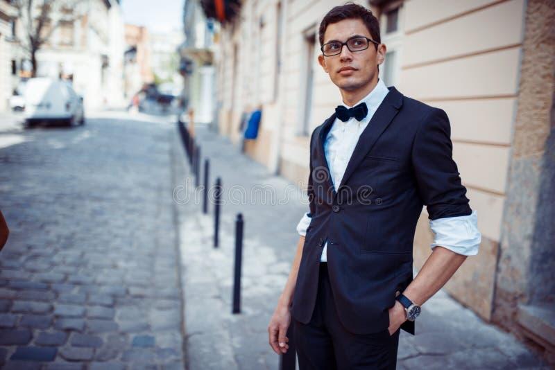 Ritratto dell'uomo ben vestito alla moda che posa all'aperto distogliere lo sguardo fotografia stock