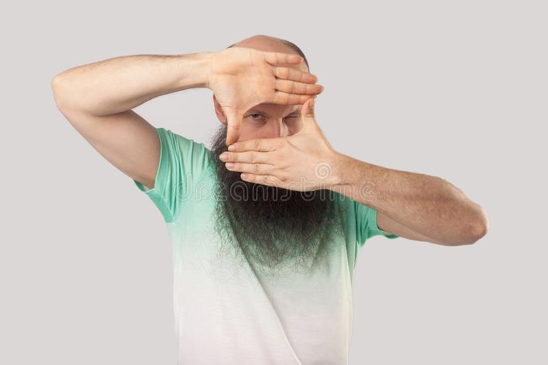 Ritratto dell'uomo calvo invecchiato mezzo attento con la barba lunga nella condizione verde chiaro della maglietta con il gesto  fotografia stock