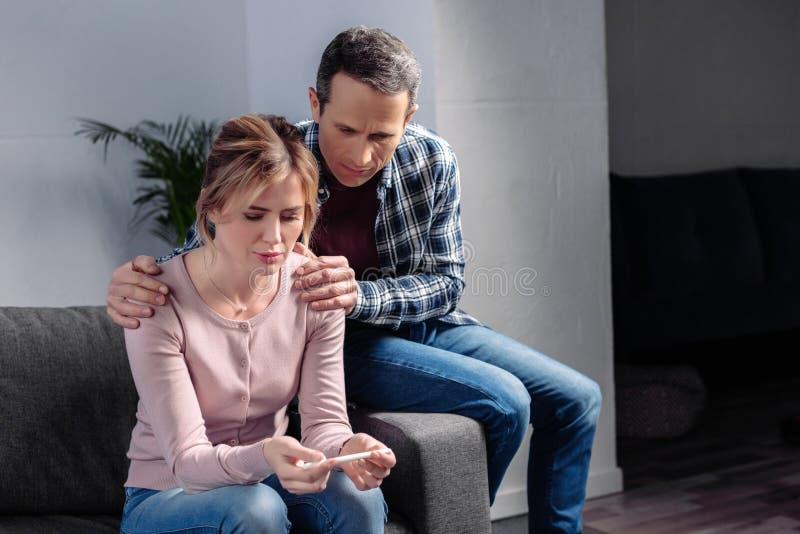 ritratto dell'uomo che abbraccia moglie triste con il test di gravidanza in mani immagine stock
