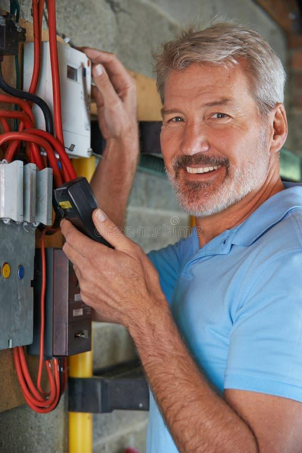 Ritratto dell'uomo che annota la lettura del tester di elettricità immagine stock