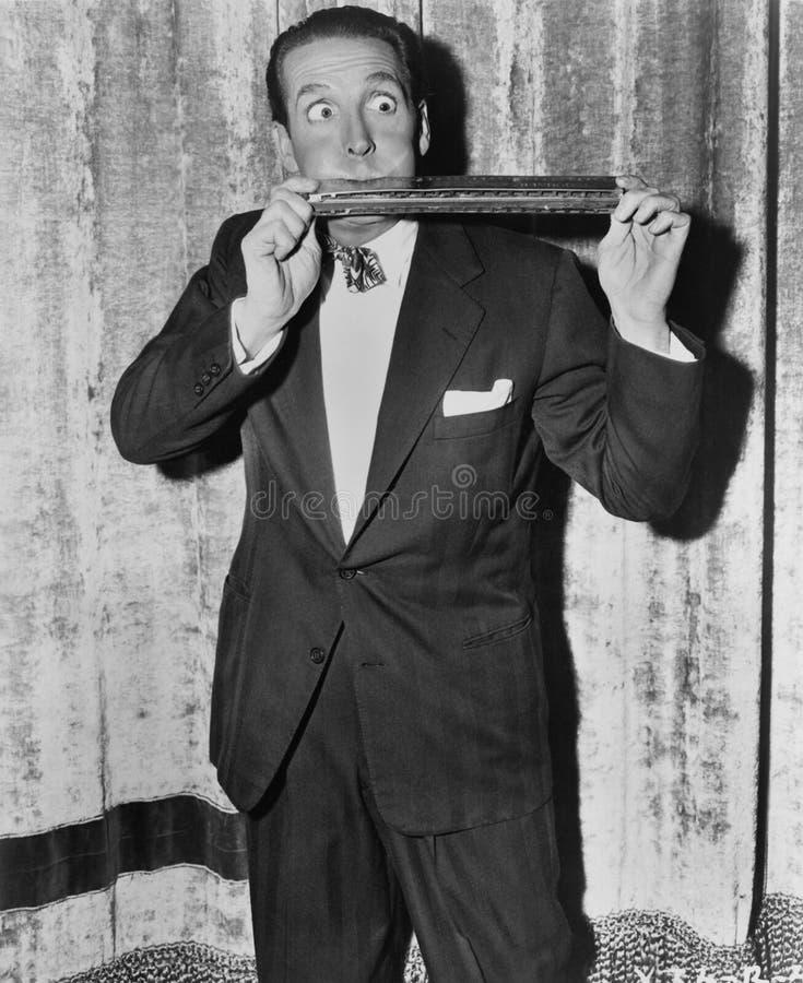 Ritratto dell'uomo che gioca armonica enorme (tutte le persone rappresentate non sono vivente più lungo e nessuna proprietà esist immagine stock