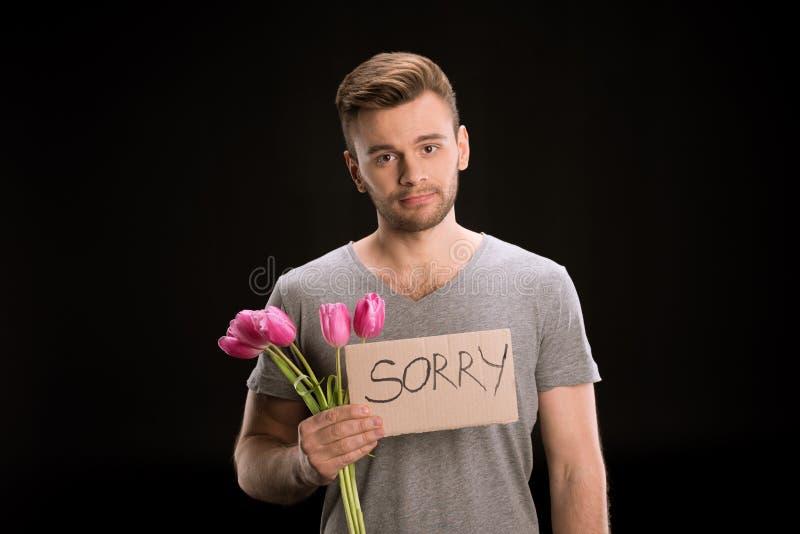Ritratto dell'uomo che guarda alla macchina fotografica mentre tenendo il mazzo dei tulipani e segno spiacente fotografia stock