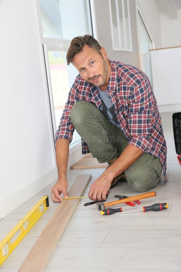 Ritratto dell'uomo che installa pavimento di legno immagine stock libera da diritti
