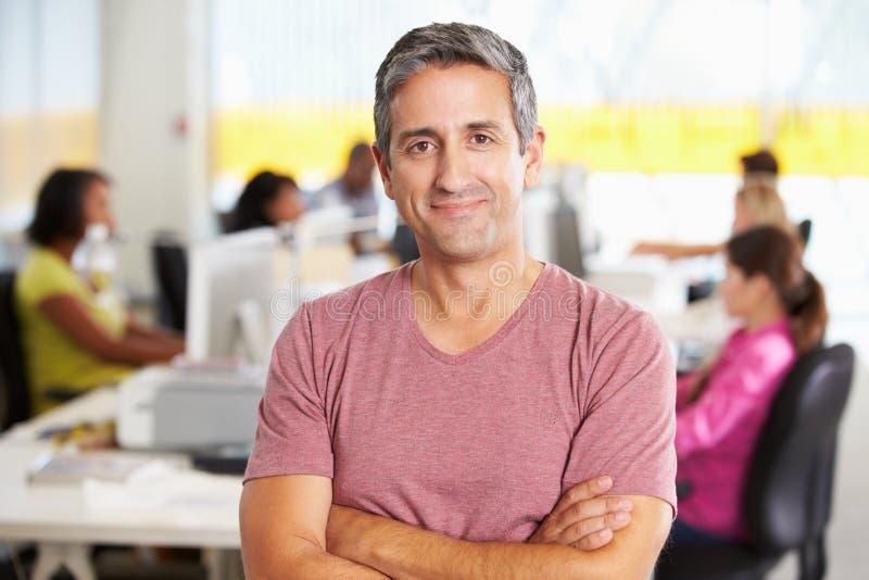 Ritratto dell'uomo che sta nell'ufficio creativo occupato immagini stock