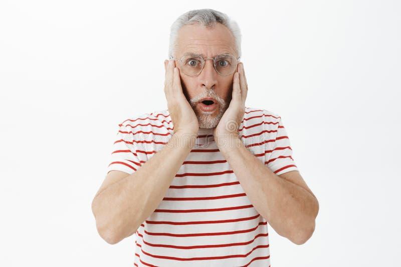Ritratto dell'uomo colpito che esamina stupito ed eccitato la macchina fotografica con la mandibola caduta che si tiene per mano  fotografie stock