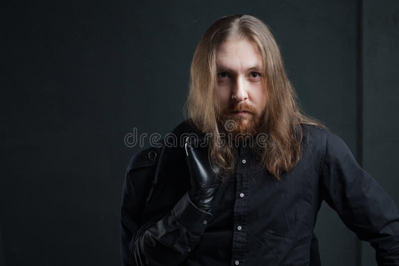 Ritratto dell'uomo con capelli lunghi e della barba in vestiti neri su fondo scuro fotografia stock libera da diritti