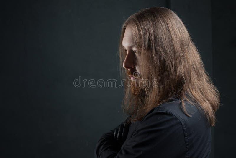 Ritratto dell'uomo con capelli lunghi e della barba in vestiti neri su fondo scuro fotografie stock