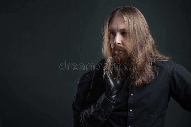 Ritratto dell'uomo con capelli lunghi e della barba in vestiti neri su fondo scuro immagine stock