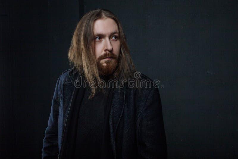 Ritratto dell'uomo con capelli lunghi e della barba in vestiti neri su fondo scuro immagini stock libere da diritti