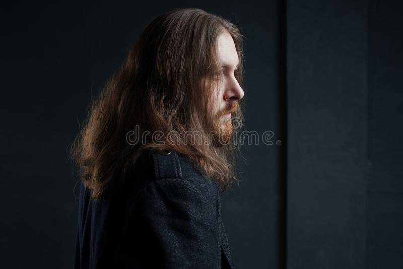 Ritratto dell'uomo con capelli lunghi e della barba in vestiti neri su fondo scuro fotografia stock
