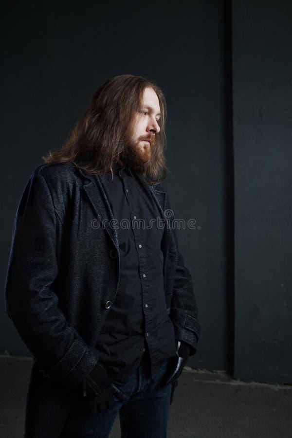 Ritratto dell'uomo con capelli lunghi e della barba in vestiti neri su fondo scuro immagine stock libera da diritti