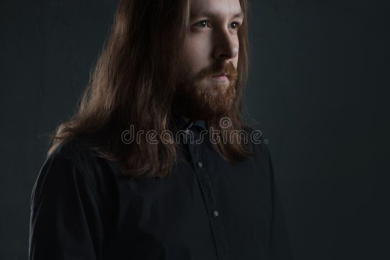 Ritratto dell'uomo con capelli lunghi e della barba in vestiti neri su fondo scuro immagini stock