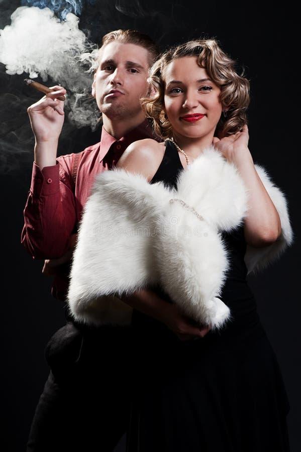 Ritratto dell'uomo con il sigaro e la donna di eleganza fotografie stock libere da diritti