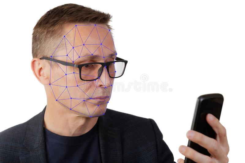 Ritratto dell'uomo con lo smartphone facendo uso del sistema di riconoscimento di identificazione del fronte immagini stock