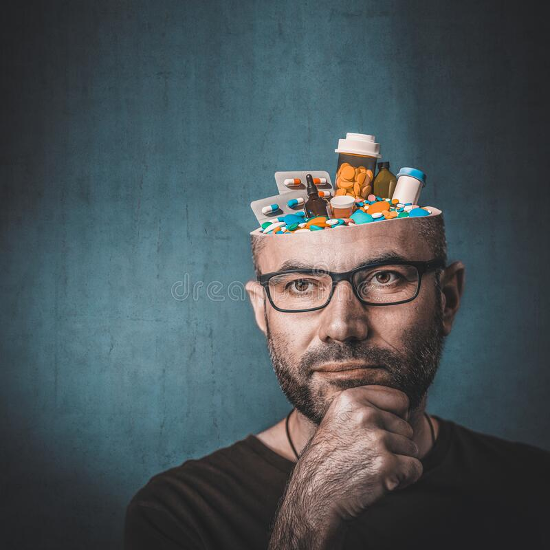 Ritratto dell'uomo con pillole in testa fotografia stock libera da diritti