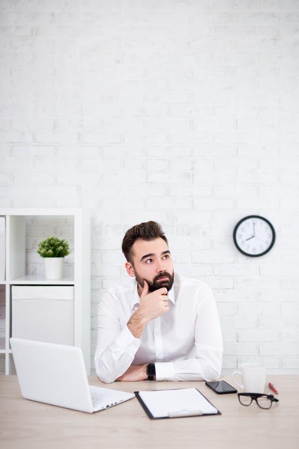 Ritratto dell'uomo d'affari barbuto bello che pensa a qualcosa in ufficio fotografia stock libera da diritti