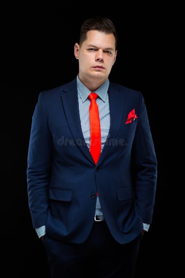 Ritratto dell'uomo d'affari bello sicuro su fondo nero fotografia stock