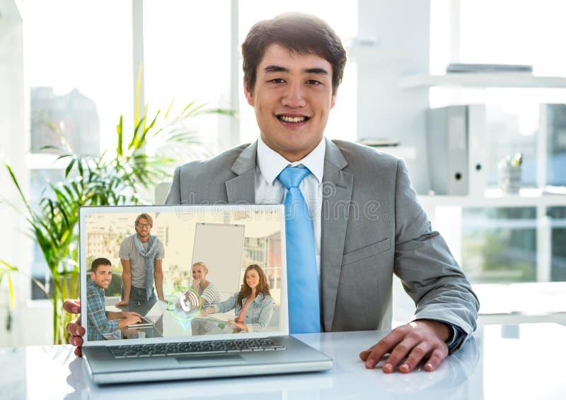 Ritratto dell'uomo d'affari che ha video chiamata sul computer portatile in ufficio fotografie stock libere da diritti