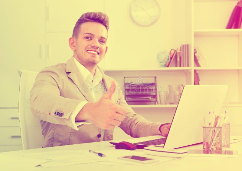 Ritratto dell'uomo d'affari che mostra i pollici su nell'ufficio moderno fotografie stock