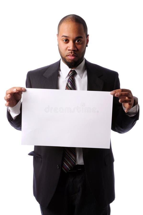 Ritratto dell'uomo d'affari che tiene segno in bianco fotografie stock
