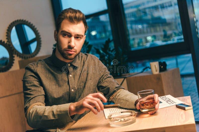 ritratto dell'uomo d'affari con il sigaro ed il vetro di whiskey in mani che si siedono alla tavola fotografie stock