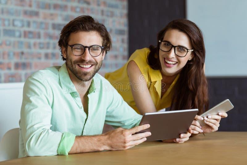 Ritratto dell'uomo d'affari e del collega che tengono compressa digitale immagini stock