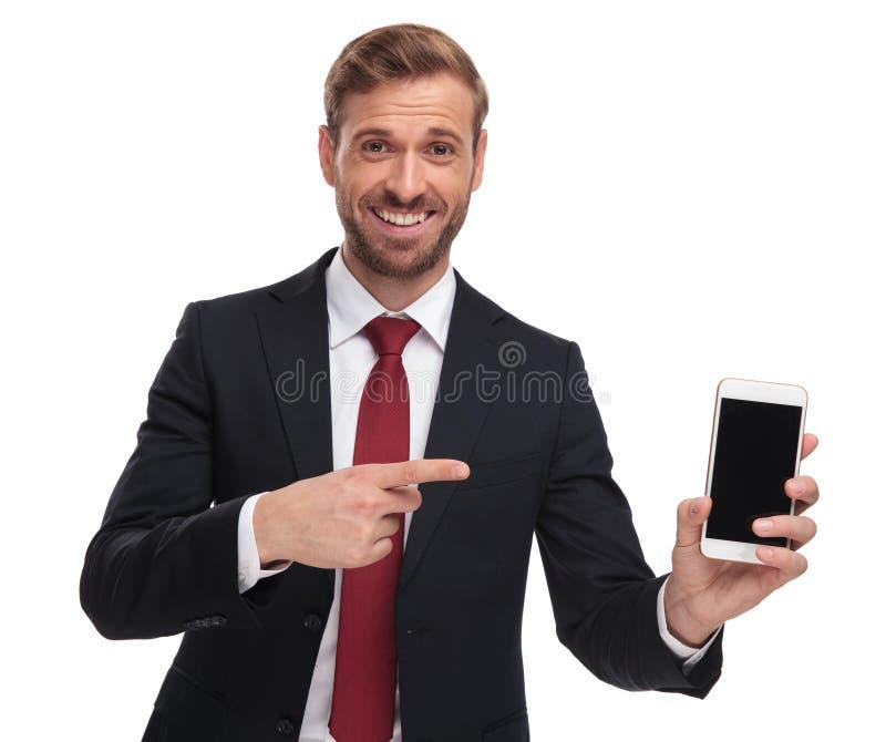 Ritratto dell'uomo d'affari felice che indica allo schermo del telefono cellulare fotografia stock