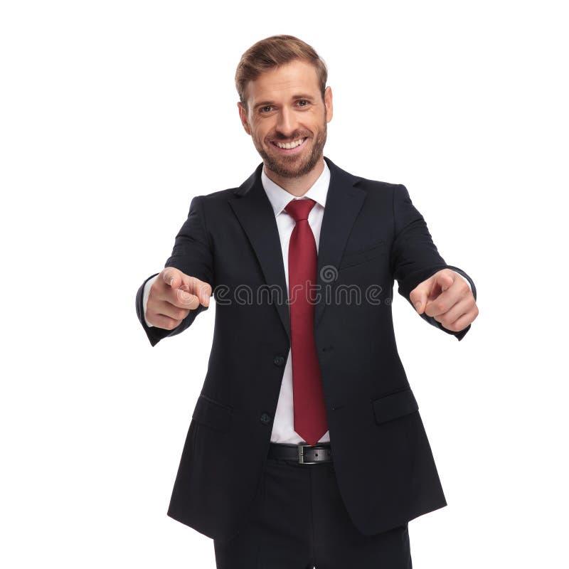 Ritratto dell'uomo d'affari felice che indica le dita mentre stando fotografia stock