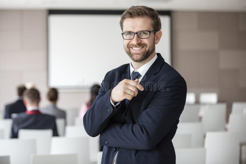 Ritratto dell'uomo d'affari felice che sta nel corridoio di seminario fotografie stock