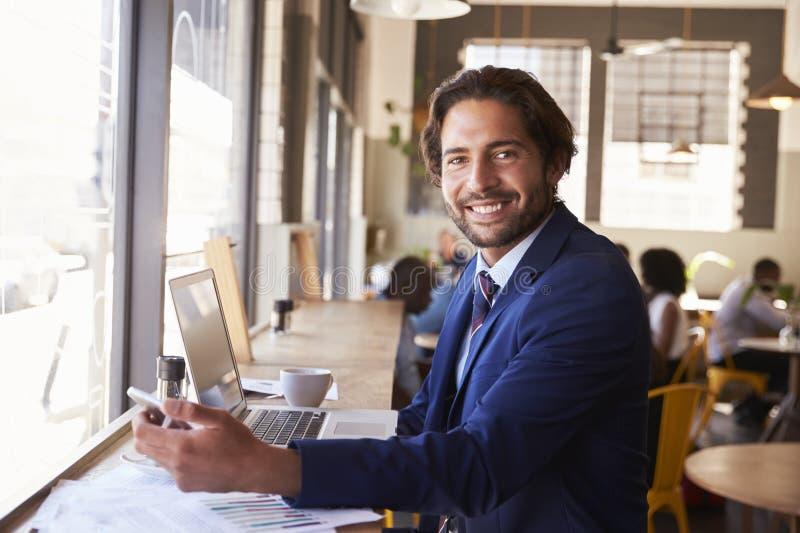 Ritratto dell'uomo d'affari With Phone Working in caffetteria fotografia stock libera da diritti