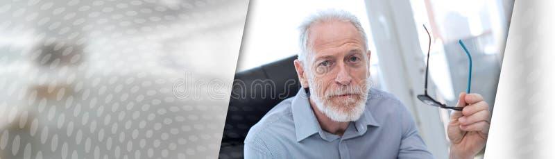 Ritratto dell'uomo d'affari senior che tiene i suoi vetri; insegna panoramica fotografia stock libera da diritti