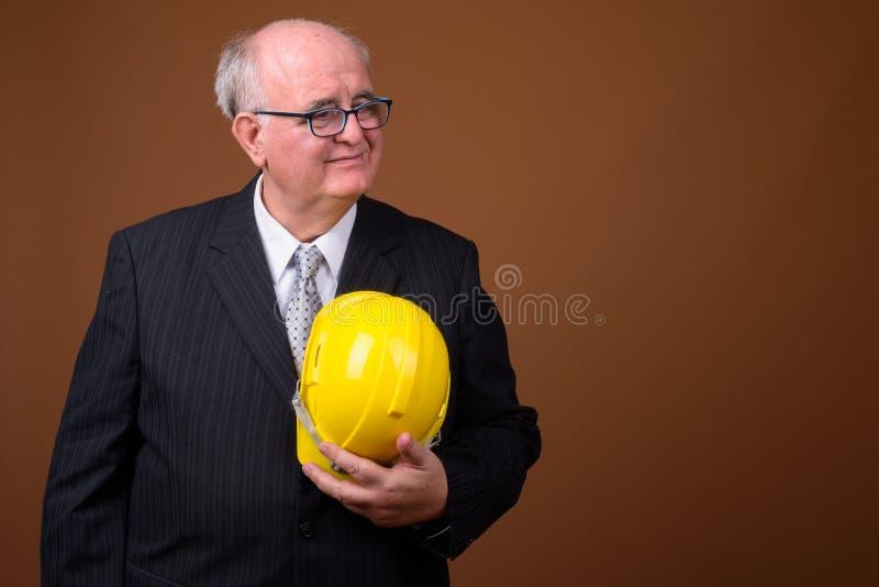 Ritratto dell'uomo d'affari senior di peso eccessivo con l'elmetto protettivo immagini stock libere da diritti