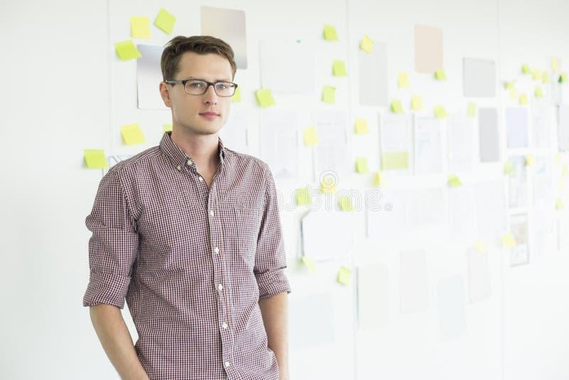 Ritratto dell'uomo d'affari sicuro che sta contro la lavagna in ufficio creativo fotografie stock