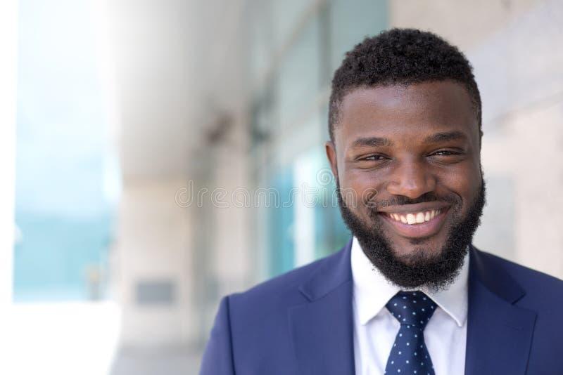 Ritratto dell'uomo d'affari sorridente nero che esamina macchina fotografica in un ambiente urbano Copi lo spazio immagini stock